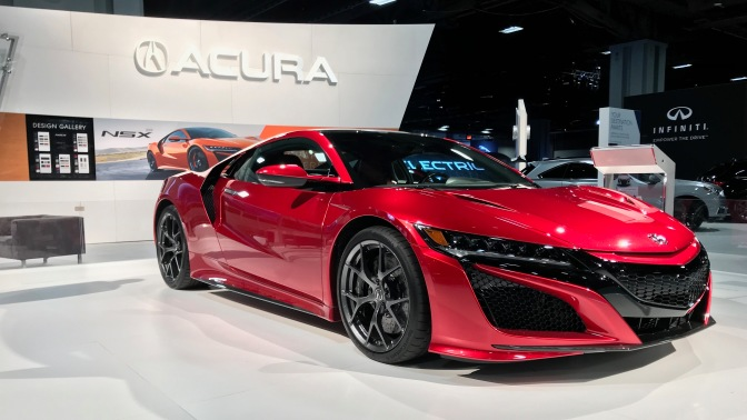 Red Acura NSX, with large Acura sign in the background.