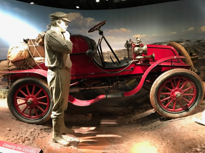 1903 Winton automobile, with a mannequin of a man representing an early auto pioneer in the foreground.