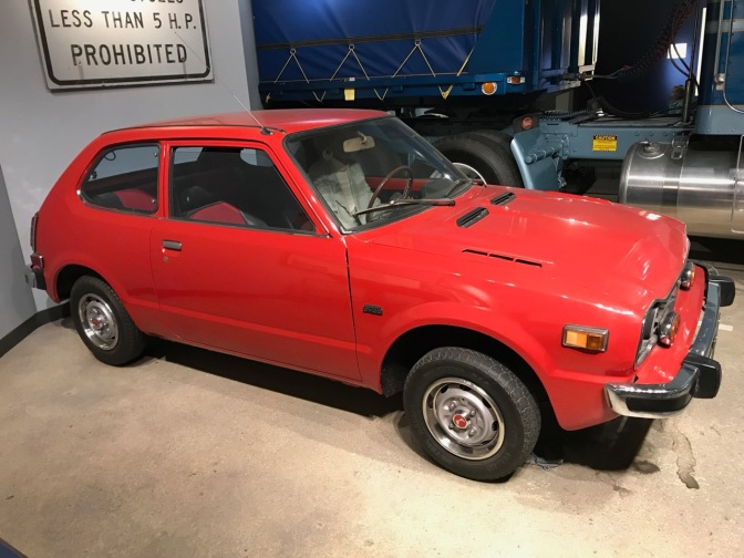 Red 1977 Honda Civic hatchback. A semi is in the background.