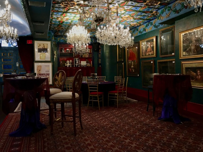 Interior of reception room of mansion, with chandeliers hanging from the ceiling, paintings on the walls, and high top tables in the foreground.
