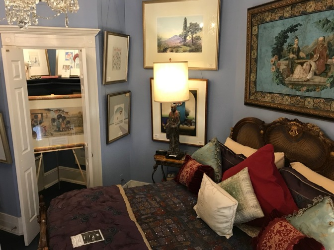 Rosa Parks room, with paintings on the wall, a bed in the foreground, and another painting in the closet.