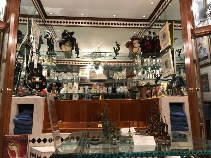 Elaborate bathtub, which chess set on glass table in front of tub. A guitar, statues, and glasses are on glass shelves behind the tub.
