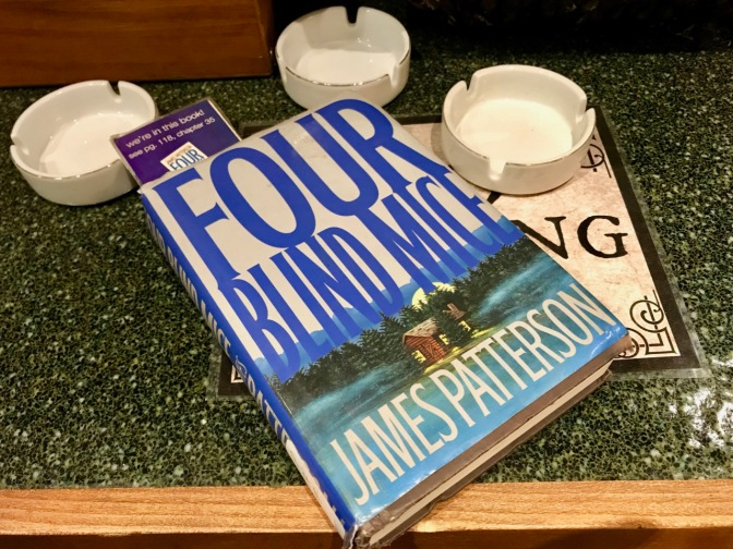 Copy of Four Blind Mice book by James Patterson, with three ashtrays in the background.
