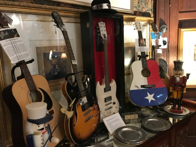 Five guitars on a sideboard, w with silver plates in the foreground.