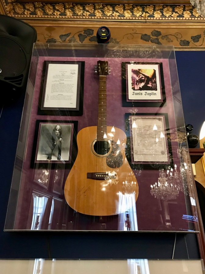 Glass case with Janis Joplin's acoustic guitar, a photo of Janis, her will, and her death certificate.