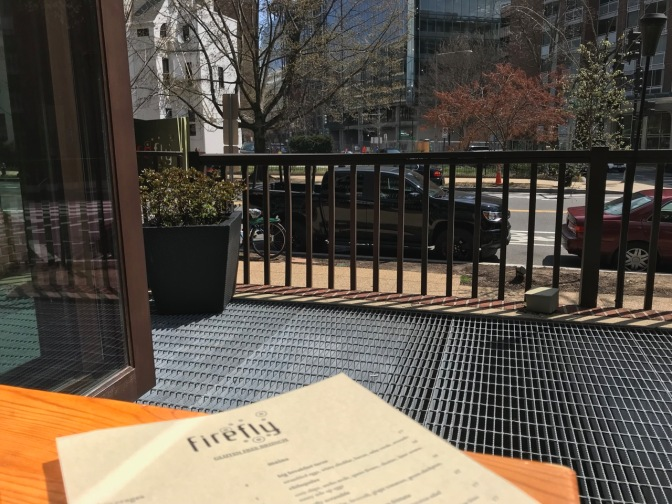 Firefly menu on table by open window, with street and buildings in view.