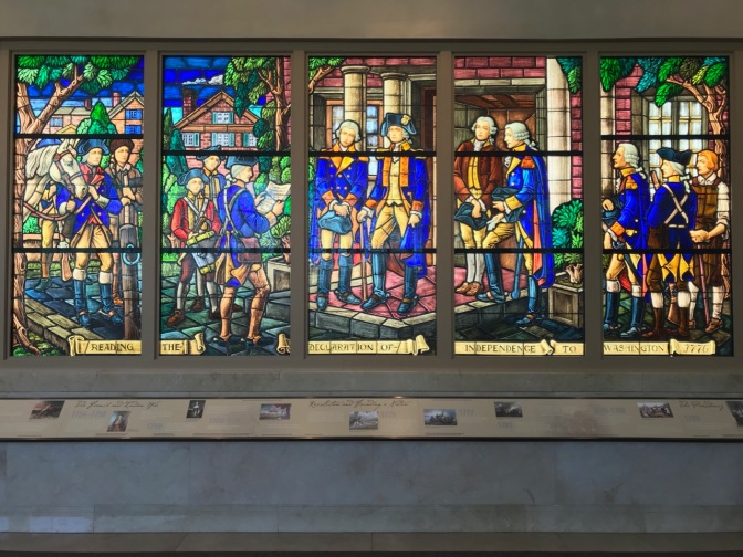 Stained glass window with the story of the reading of the Declaration of Independence to Washington.