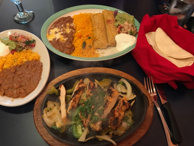 Tamales on plate with rice and refried beans. Fajita sizzling on skillet. Tortillas in basket with red cloth. Plate with lettuce, guacamole, refried beans, and rice, all on a table.