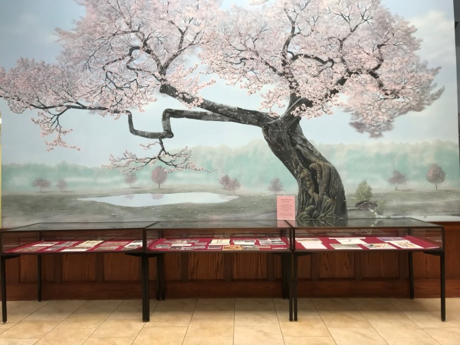 Mural of tree in front of glass display cases with information on cherry blossom trees.