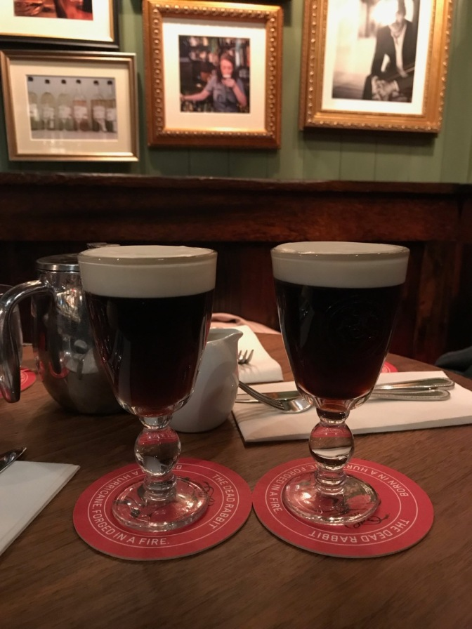 Two irish coffees in glasses on table. Framed photographs are in the background.