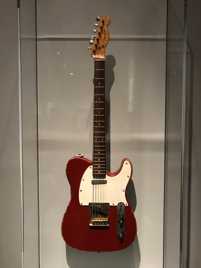 Red Fender Telecaster with white pick guard.