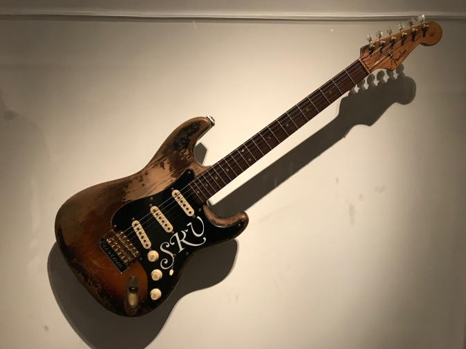Fender Stratocaster, in raw wood, with the initials SRV in white on the black pick guard.