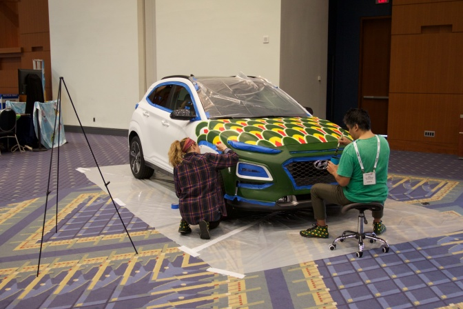 Two artists painting a Hyundai hatchback.
