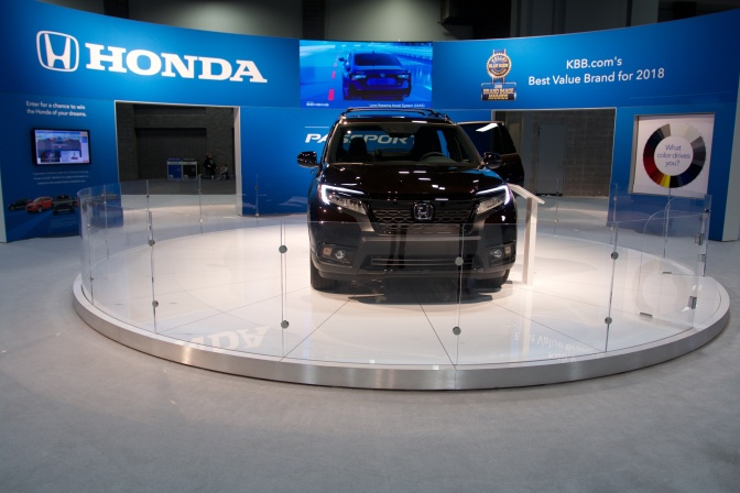 2019 Honda Passport SUV in black, on a circular pedestal in front of a Honda marquee.