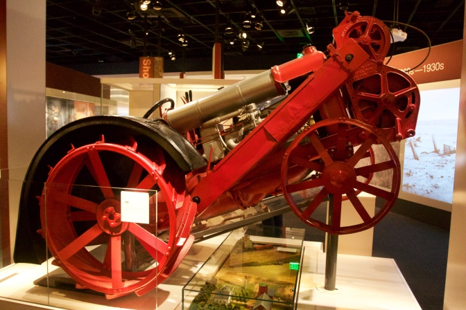 Tractor, with red and gold framework, standing on its rear wheels.