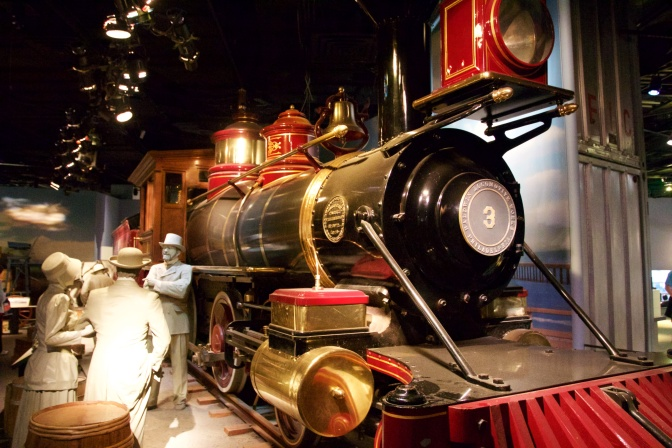 Steam locomotive, with mannequin passengers in the foreground.