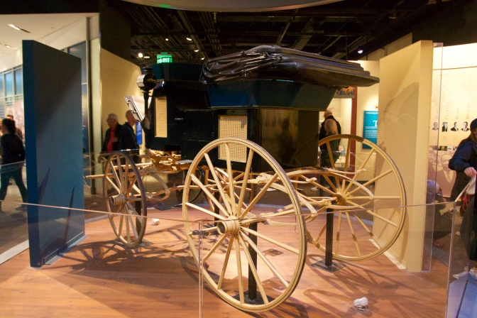 Horse-Drawn carriage, in black, with wooden wheels.