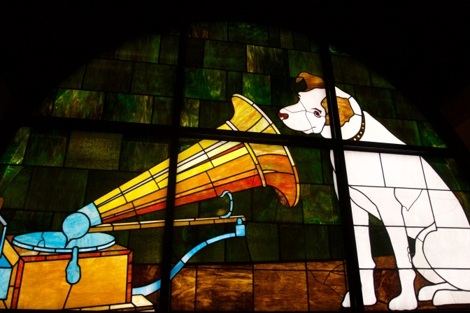 Stained glass window of white dog listening to record player.