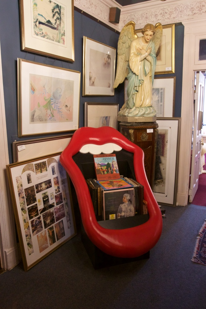 Red lips and mouth chair, angel statue, and artwork, in a corner of a room.