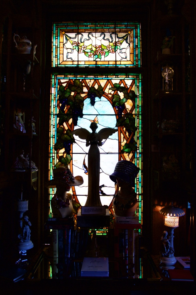 Stained glass windows, with statues in the foreground.
