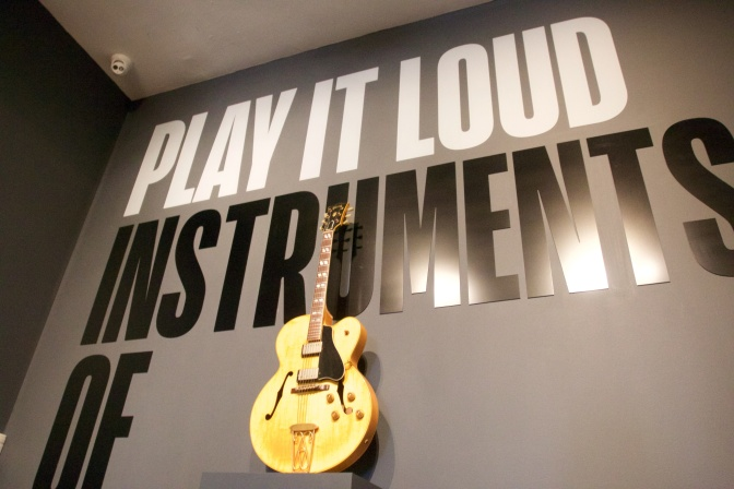 Gibson Hollow-body electric guitar in front of wall sign that says PLAY IT LOUD INSTRUMENTS OF