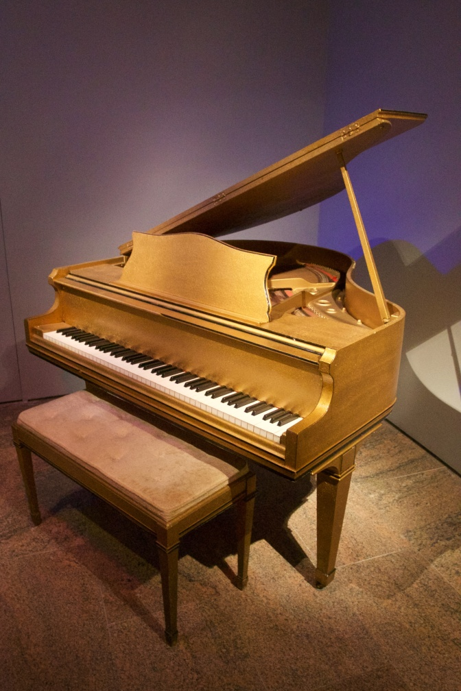 Wooden piano with top lifted. A bench is in front of the piano.