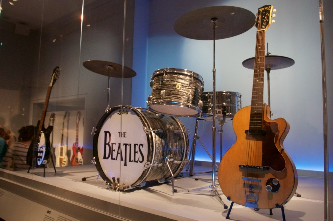 Twelve string Rickenbacker guitar, drum kit that says THE BEATLES on the bass drum, and Hofner electric guitar.