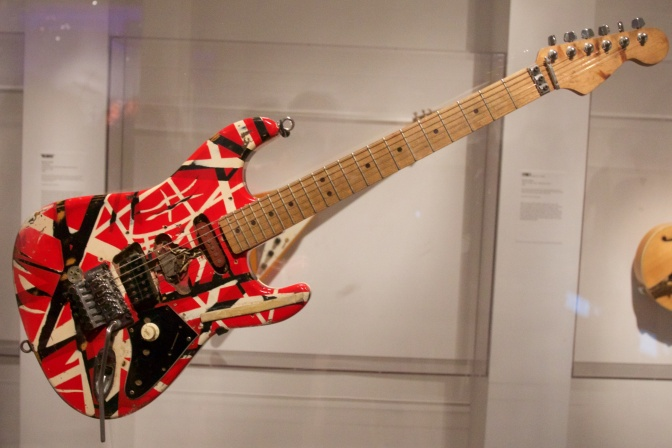 Red-White-Black Frankenstein stratocaster, hanging in clear display case.