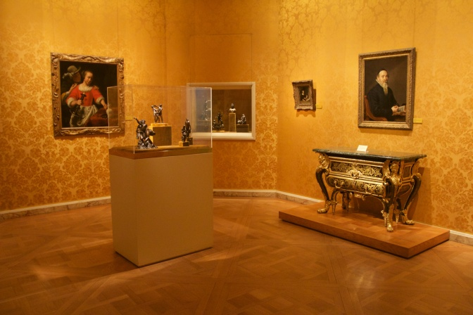 Gold wallpaper room filled with paintings and objects from 16th century Europe.