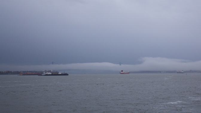 Fog covering Verrazano Narrows Bridge, with ships in the foreground.