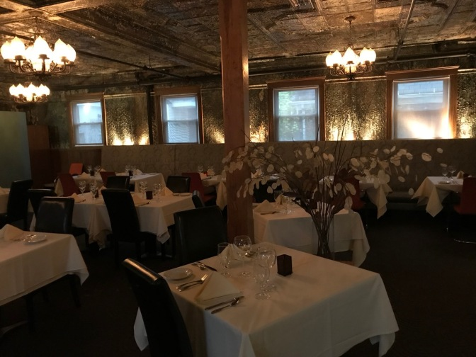 Interior of dining room of Tides Hotel. Tinwork is on ceiling and walls, and chandeliers hang from the ceiling.