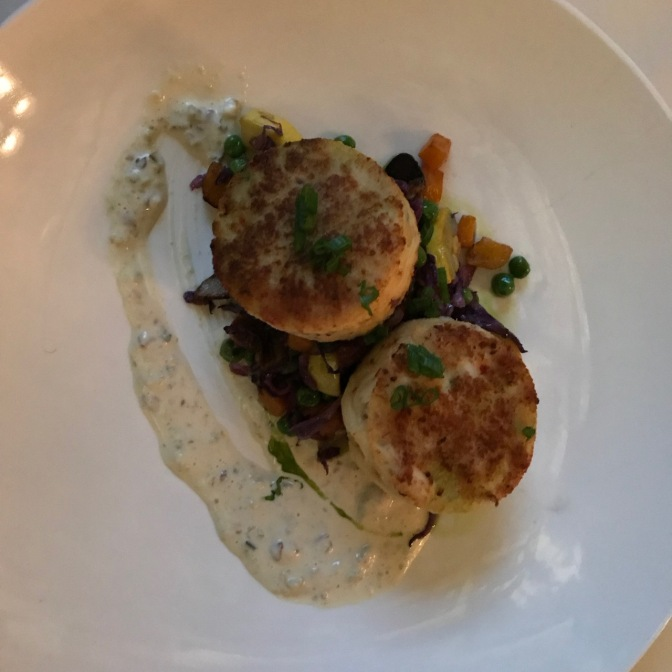 Two crab cakes on a bed of potatoes and vegetables.