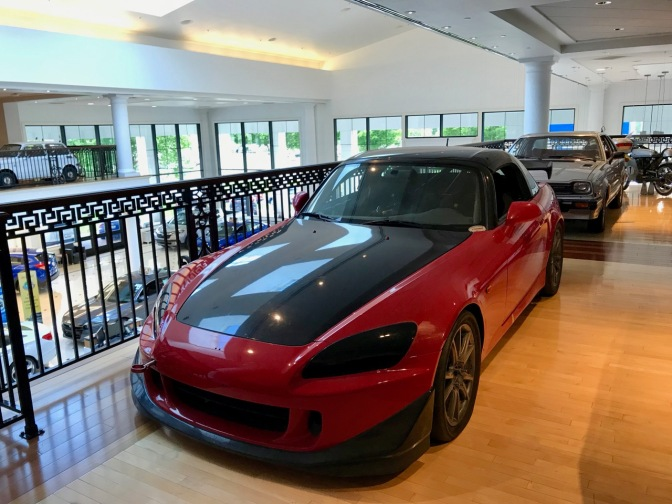 Red Honda S2000 race car, with black hood and roof.