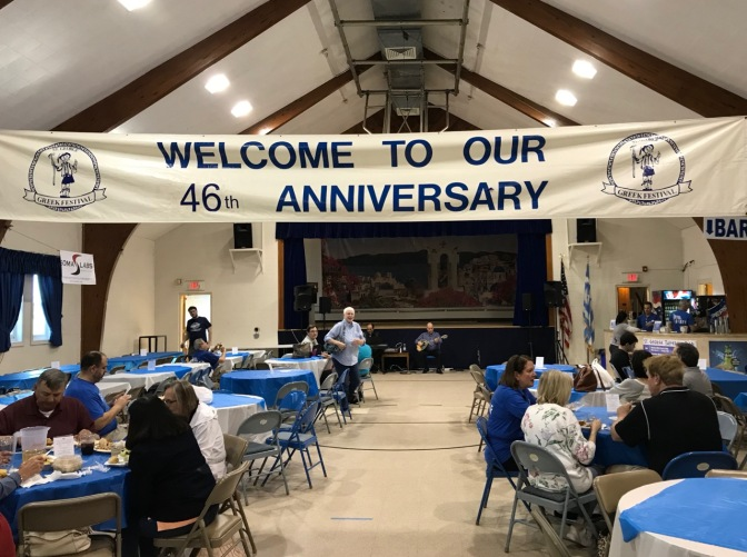 Church hall that has a sign that says WELCOME TO OUR 46th ANNIVERSARY. Musicians play at the front, while people sit at round tables.