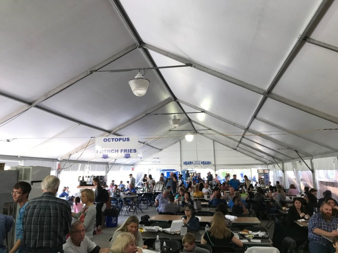 Tent with people dining. Signs point to different food stations.