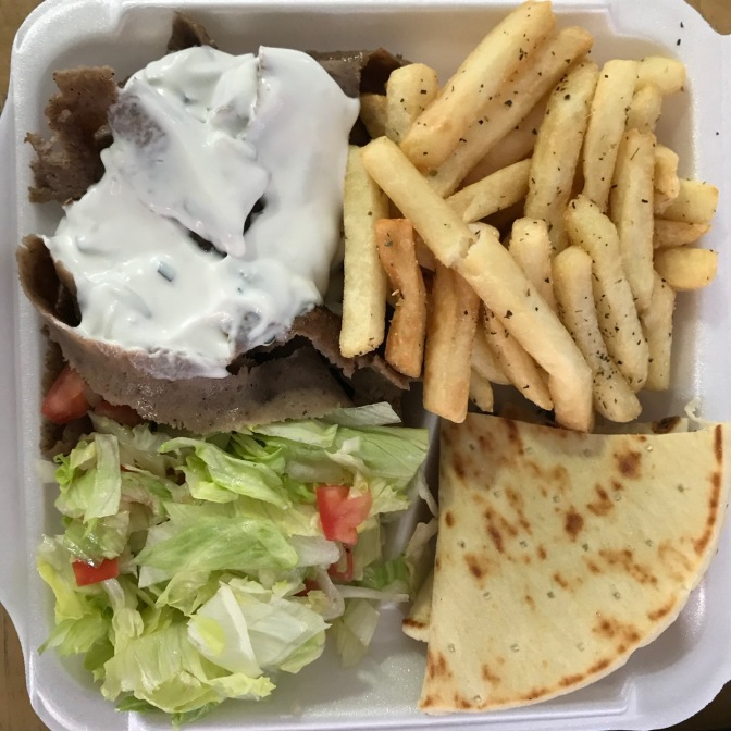 Gyro platter with lamb meat, lettuce, pita, and french fries.