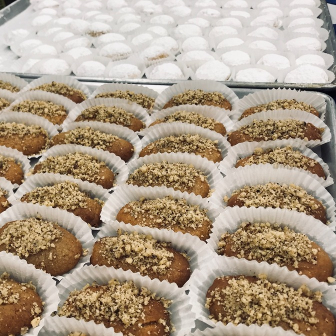 Greek pastries in rows on baking sheets.