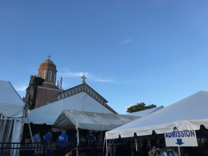 White tents in front of Greek Orthodox church (spire visible in background).