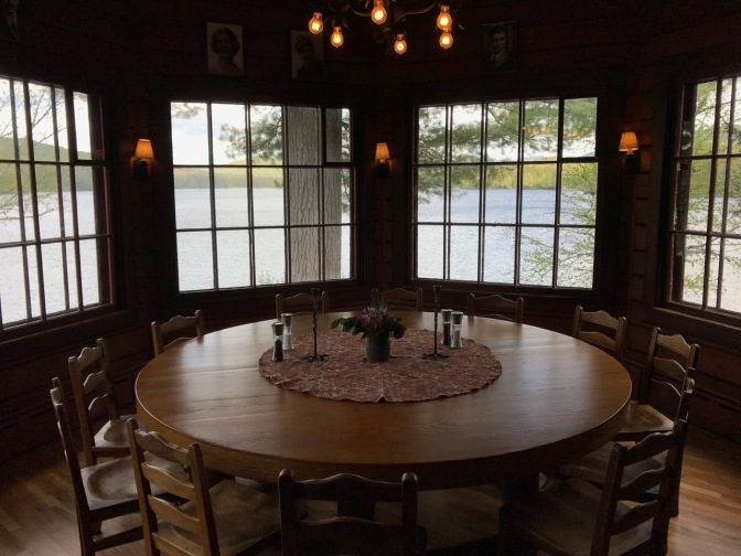 Round dining table with view of Sagamore Lake in the background.