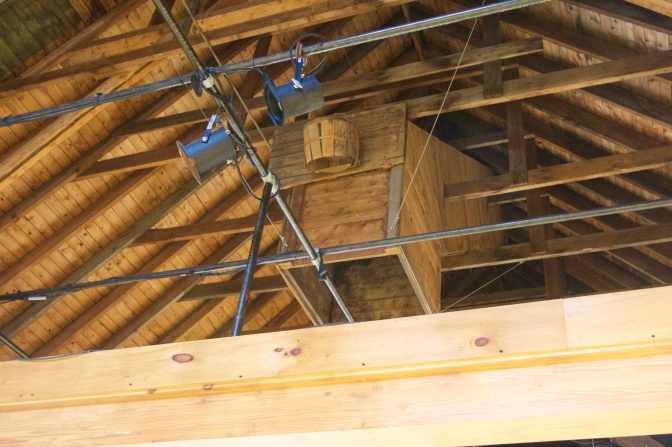 Basketball hoop made from wooden basket, in rafters of barn.