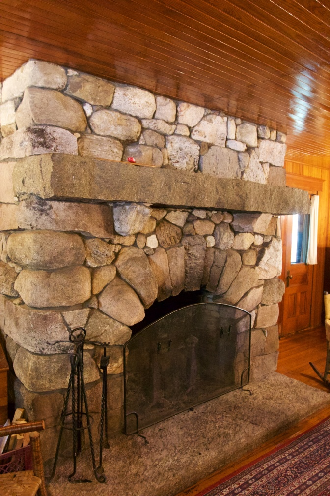 Large stone fireplace in Wigwam building.