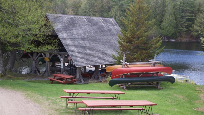 Boathouse, with canoes on a rack outside of it, and picnic tables in the foreground.