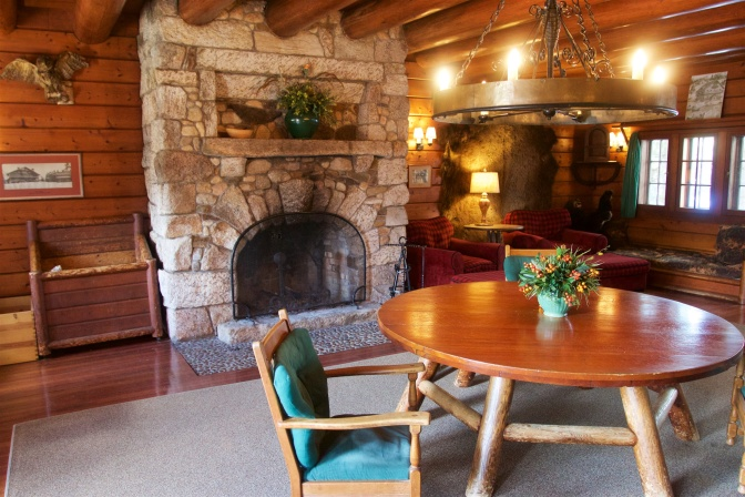 Lobby of Lodge, with chandelier, fireplace, and round wooden table with chairs.