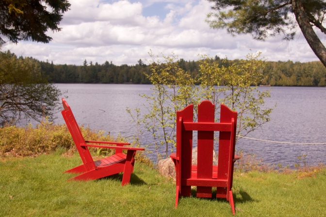 Red Adirondack Chairs by lakeside.