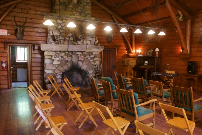 Interior of the playhouse, with wooden folding chairs in foreground and a large fireplace in the background. Several stuffed animal heads are mounted to the walls.