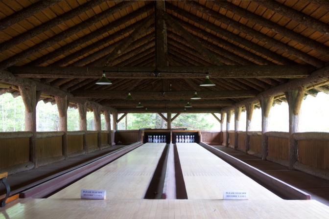 Two bowling lanes under arched roof.