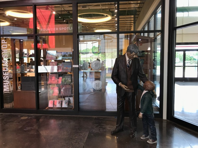 Statue of man and child standing in front of gift shop in welcome center.