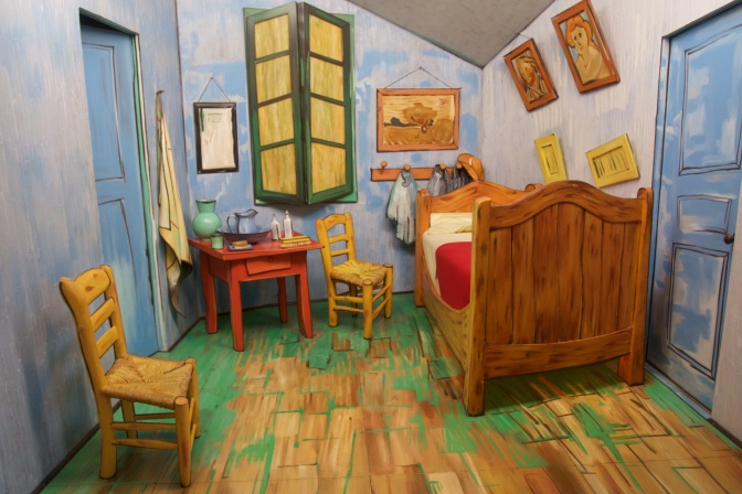 Sculpture of bedroom with bed, chairs, window, door, small table, and paintings.