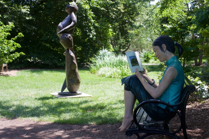 Sculpture of woman reading on a bench.