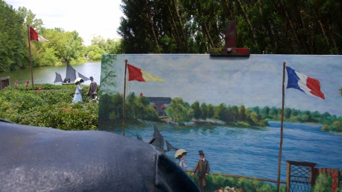 Easel with painting of lake, with lake scene in background.
